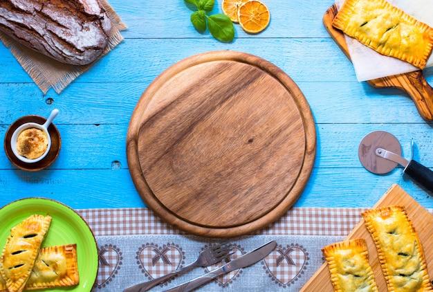 木製の背景に、家庭で作られたほうれん草のおいしいパイ、
