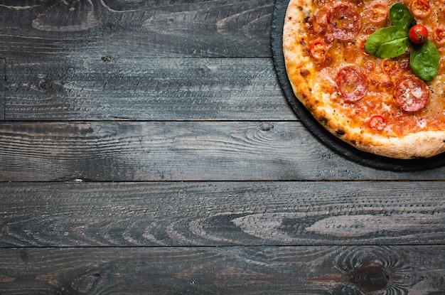 素朴な木製のテーブルに熱いイタリアのピザ。