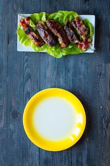 Жареные свиные ребрышки барбекю с овощами на деревянном фоне;