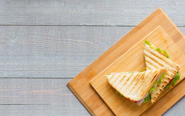 木製の背景にヘルシーなサンドイッチトーストのトップビュー