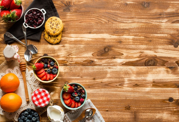 Крупа. завтрак с мюсли и свежие фрукты в мисках на деревенском деревянном фоне,