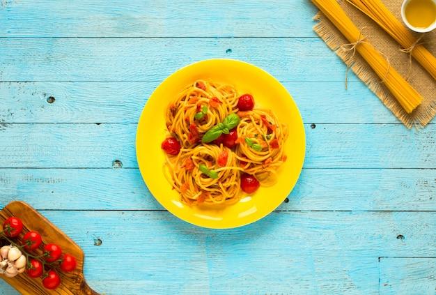 Паста с томатным соусом и другими компонентами на светло синий деревянный стол свободное место для текста.