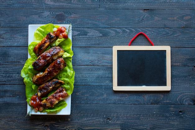 木製テーブルの上の野菜とバーベキューポークリブのグリル