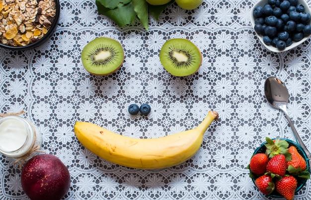 Здоровые хлопья для завтрака с бананом яблока голубики клубник югурта на деревенском деревянном. вид сверху
