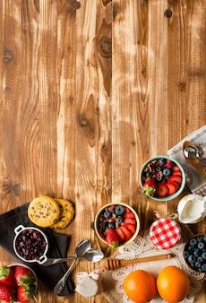 穀物。ミューズリーと素朴な木製の背景にボウルに新鮮な果物の朝食