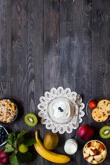 Здоровый завтрак, хлопья с йогуртом, клубникой, черникой, яблоком, бананом по дереву