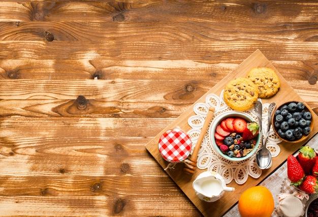 穀物。ミューズリーの朝食、木のボウルに新鮮な果物
