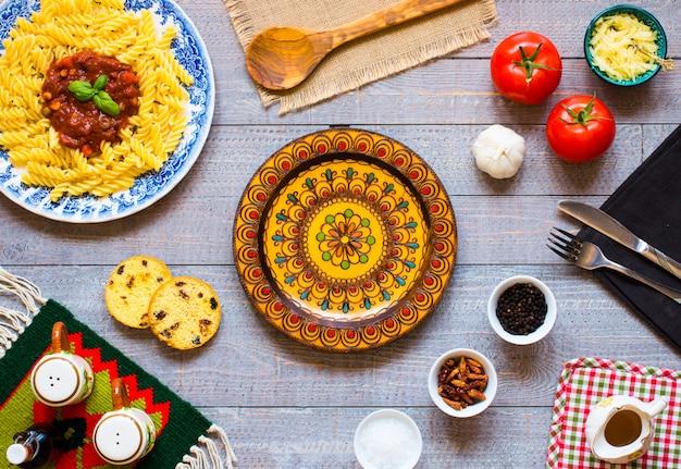トマトソース、トマト、タマネギ、ニンニク、乾燥パプリカ、オリーブ、コショウ、木の上のオリーブオイルのフジッリパスタ