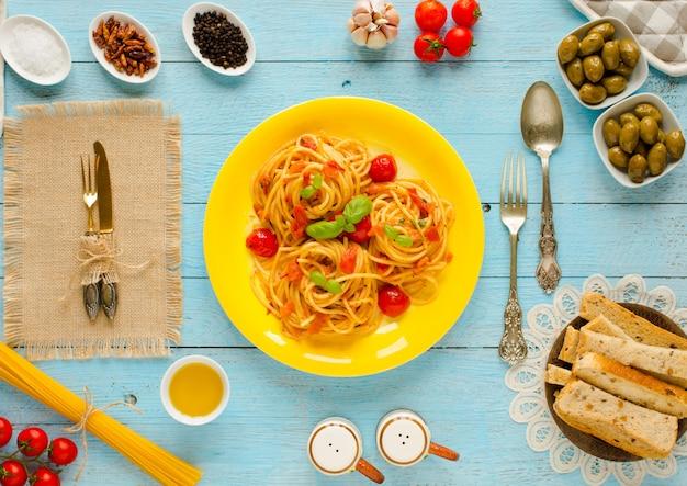 Паста с томатным соусом и другими компонентами на светло-голубом дереве
