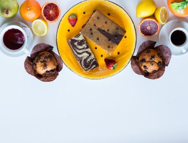 白い木製のテーブルにさまざまなペストリーや果物とコーヒーと紅茶を朝食します。