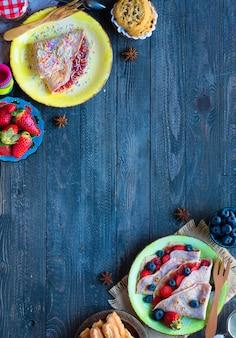 新鮮な自家製クレープ、イチゴとブルーベリー、暗い背景の木のプレートで提供しています