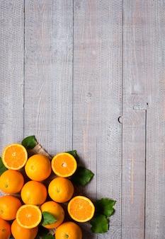木製の背景の葉と新鮮なオレンジ。上面図、