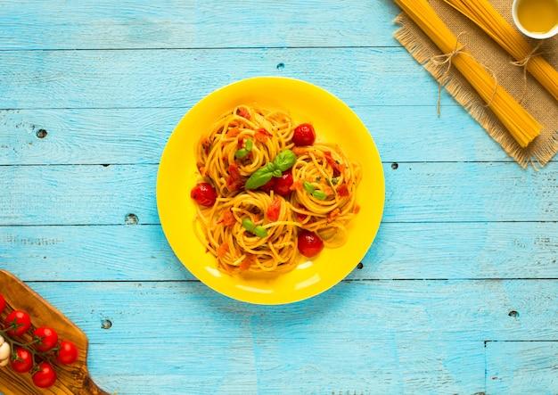 Паста с томатным соусом и другими компонентами на голубом деревянном столе,