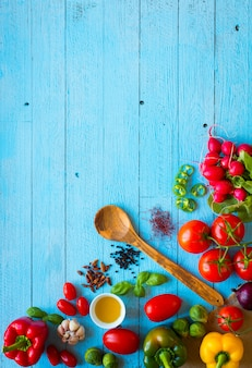 ピーマン、トマト、オリーブオイル、バシのようなイタリアのパスタ成分の完全な木製テーブルのトップビュー
