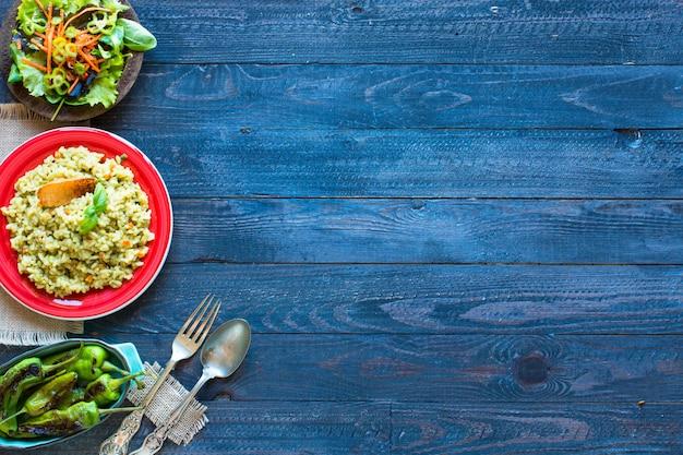 木製の素朴なテーブルで、さまざまな野菜のベジタリアンリゾット。