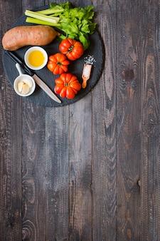 古い木製のテーブル、背景に野菜の種類