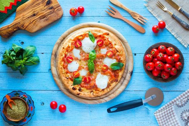 トッピングの木製テーブルの上のイタリアの古典的なピザマルゲリータのトップビュー