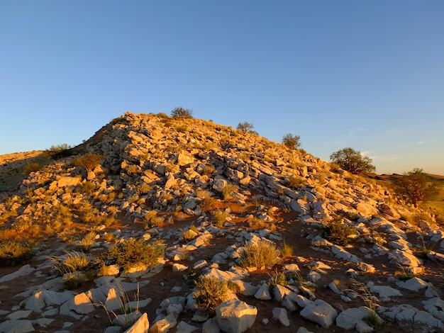 日没、ソーサスフライ、ナミビアのナミブ砂漠の大きな岩