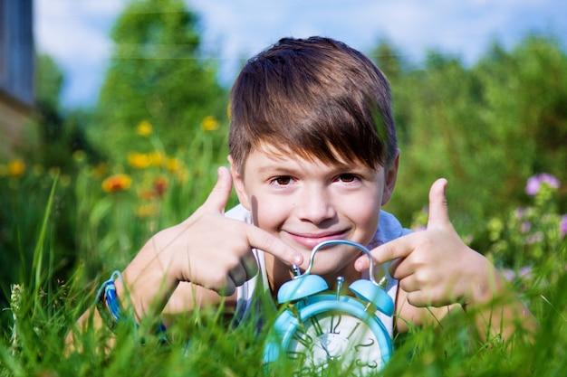 夏の庭で目覚まし時計を持つ少年を産む