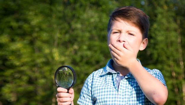 Шокирован мальчик с увеличительным стеклом летом