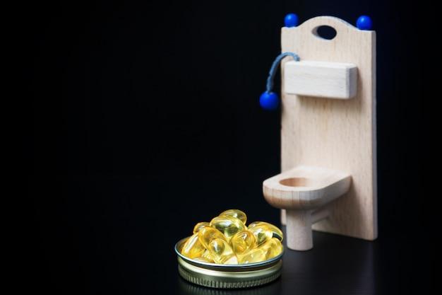 木のおもちゃのトイレと黄色のカプセル