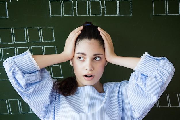 Удивленная девушка в очках сидит на доске в классе