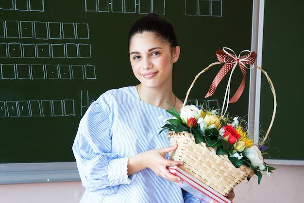 Улыбающийся студент стоит возле доски в классе