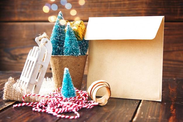 生分解性のピートモス、クラフト封筒、小さなそり、木の削りくずの人工の小さなクリスマスツリー。