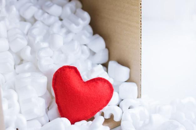 Красное войлочное сердце в упаковочной коробке, наполненной многими белыми гранулами пенопласта