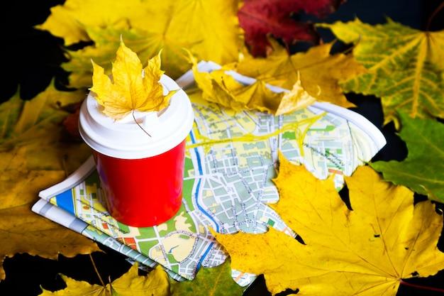 Путешествие осенью. кофе с собой, листья, карта на черном фоне