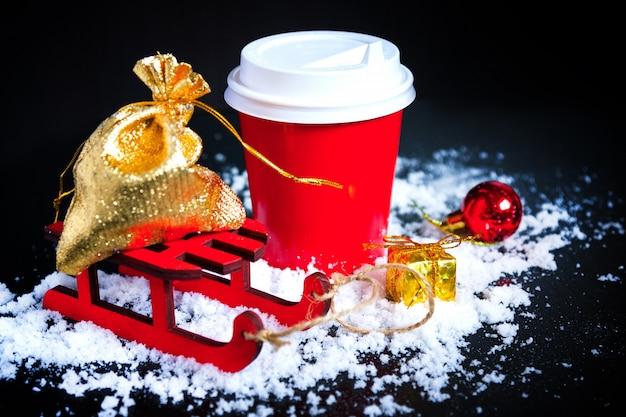 黒の背景にクリスマスプレゼントと赤カップのコーヒー