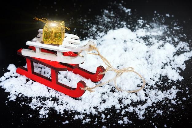 Деревянные красные и белые санки с золотым подарком на черном фоне со снегом