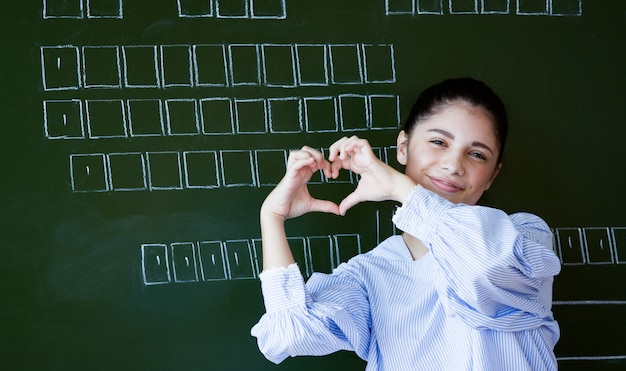 試験の彼女の愛を示すために心のジェスチャーを作る大学の教室に立っている笑顔の魅力的な若い女の子