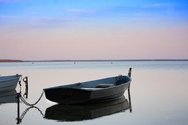 夕暮れ時の湖の上のチェーンと古い漁船