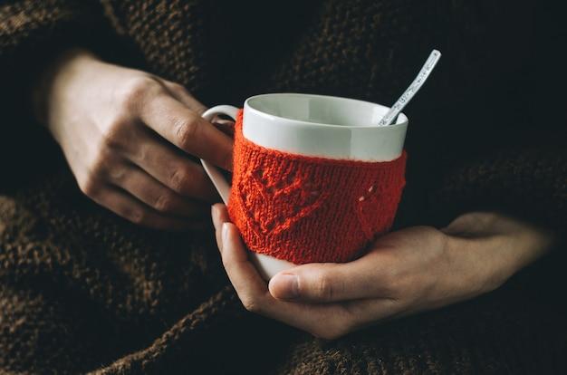 女性の手でハート柄の赤いニットウールカップ。