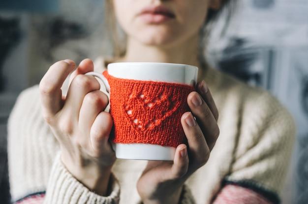 Молодая женщина пьет горячий кофе