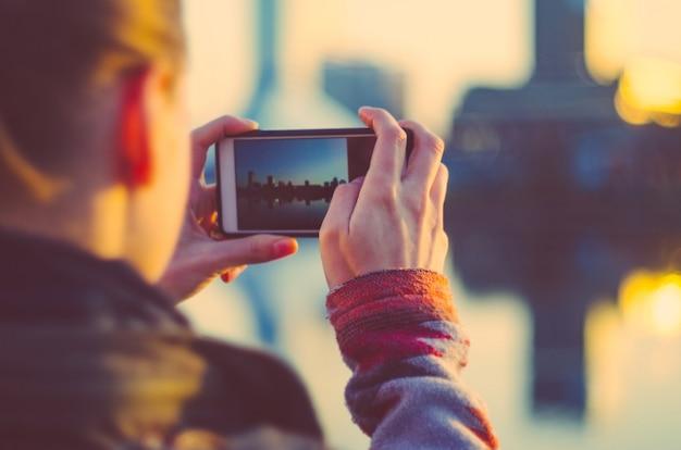 若い女性は、スマートフォンで街の写真を撮る