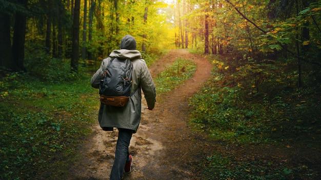 バックパックを持つ男は、素晴らしい秋の森を歩きます。