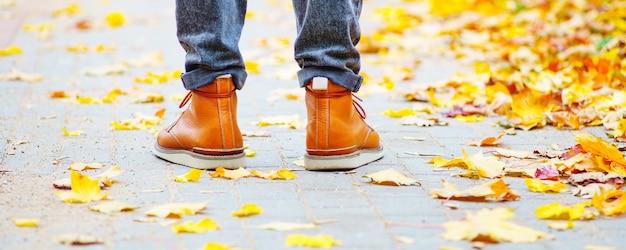 落ち葉が散らばって歩道に茶色のブーツの男の足。