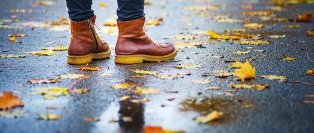 Прогулка по мокрому тротуару. вид сзади на ноги женщины, стоящей на асфальтовой мостовой с лужами под дождем. пара обуви на скользкой дороге осенью. абстрактный пустой бланк осенней погоды