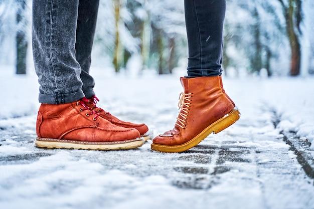 茶色のブーツで雪に覆われた歩道上のカップルの足