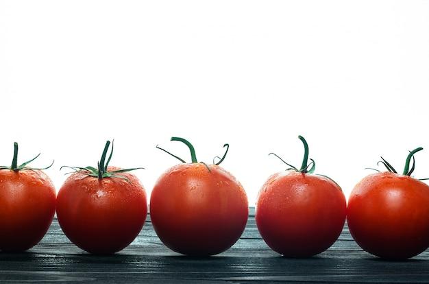 黒いテーブルの上の行に立っている赤いトマト