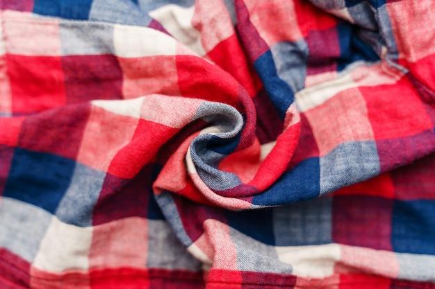 格子縞の素材のテクスチャ。赤、青、白のケージの服の背景