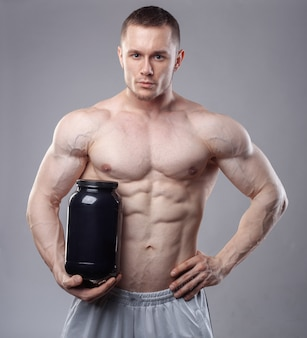 灰色の背景にホエイプロテインと黒いプラスチック瓶を保持しているボディービルダー