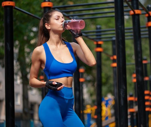 Спортивная женщина пьет витаминную воду в уличном спортзале