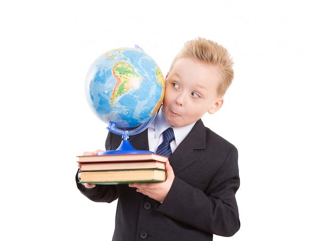 Забавный мальчик в костюме с глобусом на книгах. готов вернуться в школу