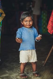 Маленькая индийская девушка в грязной одежде