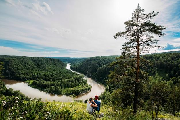 カップルが座って、川の近くの美しい夕日を見ます。男と女は川を見て、自然を楽しみます。