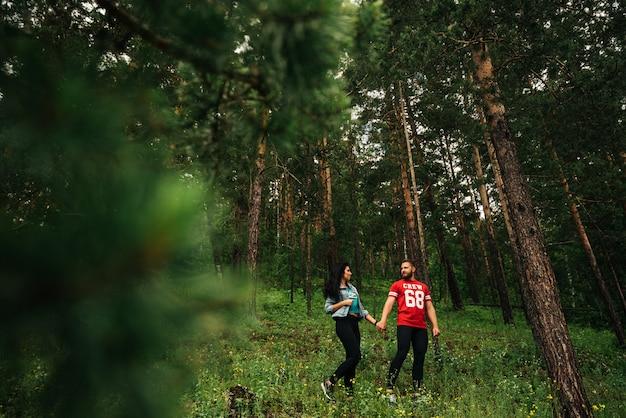 愛のカップルが針葉樹林を歩きます。男と女が森の中を歩きます。男と女が手を繋いでいます。緑の森のカップル。愛のカップルは森で手をつないでいます。フォローしてください
