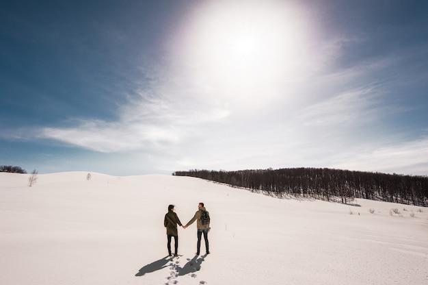 愛のカップルは、雪の中で冬に歩きます。男と女の旅行。山の愛のカップル。山の旅行者。冬の散歩。冬の冒険。冬の散歩。愛するカップル